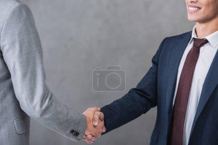 cropped shot of businessmen in formal wear shaking hands on grey