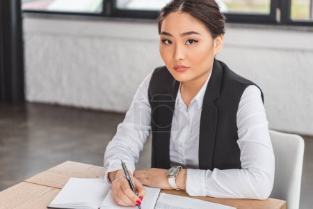serious asian businesswoman writing in notebook and looking at camera in office