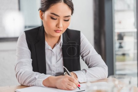 Photo for Beautiful focused young kazakh businesswoman writing in notebook at workplace - Royalty Free Image