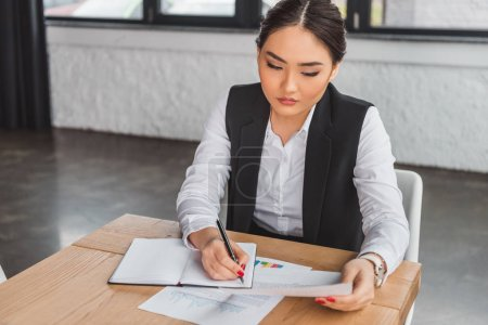 Photo for High angle view of concentrated asian businesswoman taking notes and working with papers in office - Royalty Free Image