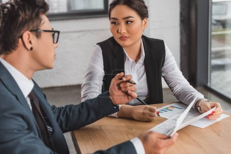 young asian business people looking at each other while working with documents in office