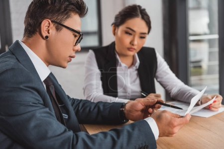 Photo for Concentrated young asian business colleagues discussing papers at workplace - Royalty Free Image