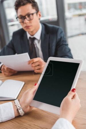 cropped shot of businesswoman using digital tablet with blank screen at workplace