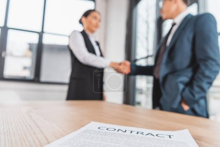 close-up view of contract on table and business people shaking hands behind
