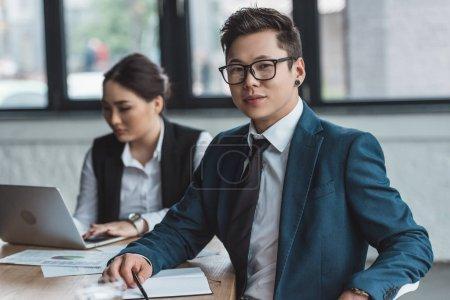 Photo pour Beau jeune entrepreneur asiatique à lunettes, souriant à la caméra tout collègue à l'aide de portable derrière au bureau - image libre de droit