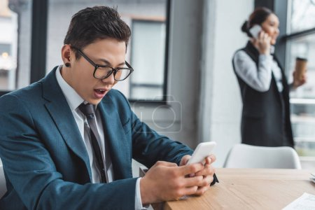 emotional young asian businessman using smartphone and female colleague talking behind in office