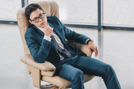 Photo pour Confiant homme d'affaires asiatique à lunettes assis avec la main sur le menton au bureau - image libre de droit