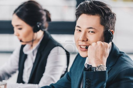 handsome young man in headset smiling at camera while working with female colleague in call center