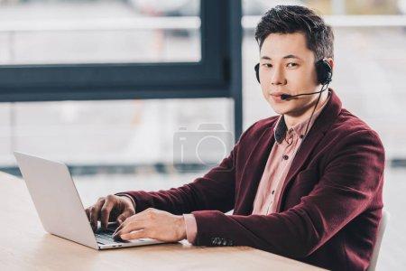 beau jeune homme d'affaires kazakh dans casque en utilisant un ordinateur portable et en regardant la caméra dans le bureau