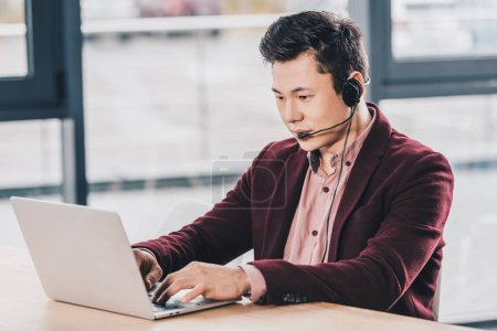 handsome young kazakh businessman in headset using laptop at workplace