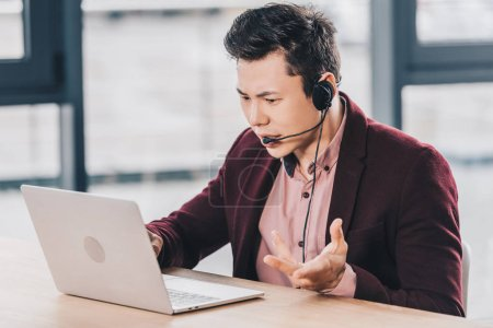 emotional young asian businessman in headset using laptop at workplace