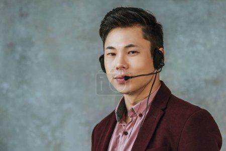 Foto de Guapo joven asiática llamada operador mirando a cámara en gris - Imagen libre de derechos