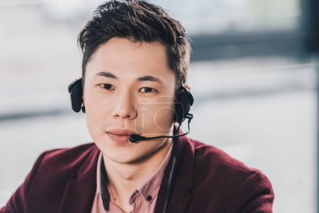 handsome young asian manager in headset looking at camera in office