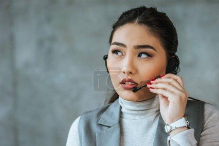 Foto de Grave joven empresaria asiática auriculares mirando lejos en gris - Imagen libre de derechos