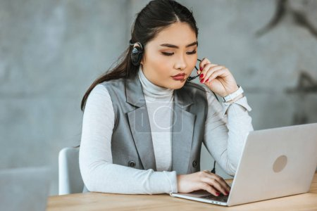 Photo for Young asian businesswoman in headset using laptop at workplace - Royalty Free Image