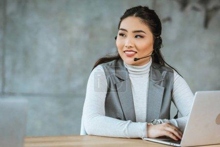 souriant jeune femme d'affaires dans un casque à l'aide d'un ordinateur portable et regardant loin dans le bureau
