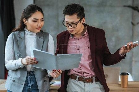 Photo pour Jeunes collègues asiatiques regardant dossier avec des papiers de bureau - image libre de droit