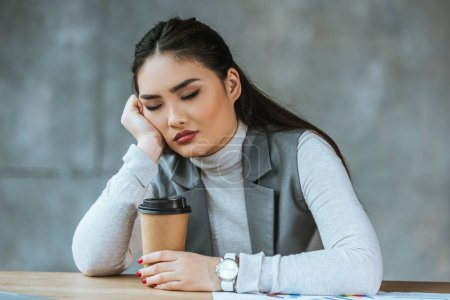 Photo for Tired young businesswoman holding coffee to go and sitting with closed eyes at workplace - Royalty Free Image