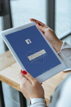 Photo pour Recadrée tir de femme d'affaires à l'aide de tablette numérique avec facebook app à l'écran - image libre de droit