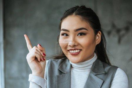 Photo pour Belle femme d'affaires kazakh vers le haut avec le doigt et souriant à la caméra - image libre de droit