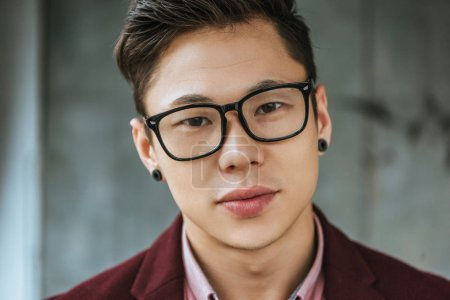 close-up portrait of handsome young asian man in eyeglasses looking at camera