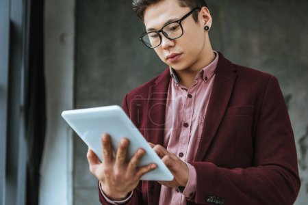 Photo for Focused young man in eyeglasses using digital tablet in office - Royalty Free Image