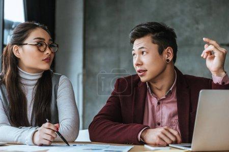 Photo pour Gens d'affaires asiatiques jeunes parler en regardant les uns les autres tout en travaillant au bureau - image libre de droit