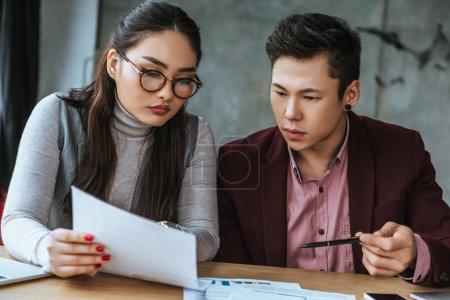 Photo pour Axé sur les jeunes collègues asiatiques en regardant les papiers au bureau - image libre de droit