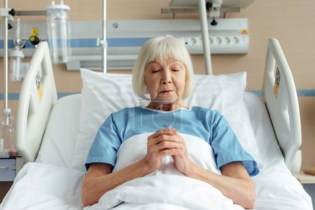 Photo for Senior woman lying in bed with folded hands and praying in hospital - Royalty Free Image