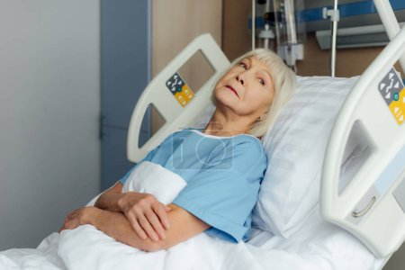 senior woman with hands crossed lying in bed in hospital