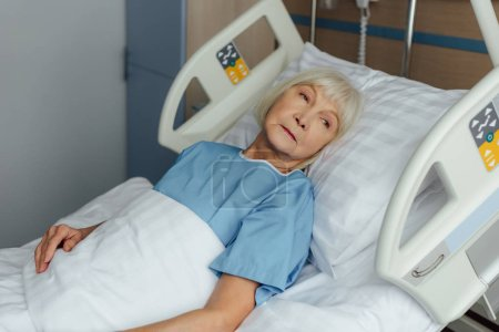 sad senior woman lying in bed in hospital and looking away