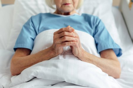 cropped view of senior woman lying in bed with folded hands and praying in hospital