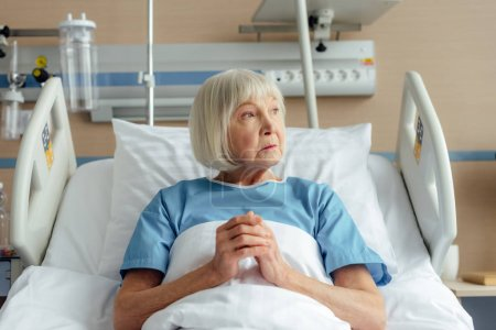 sad senior woman lying in bed with folded hands and praying in hospital