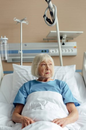senior woman lying in bed in hospital and looking away