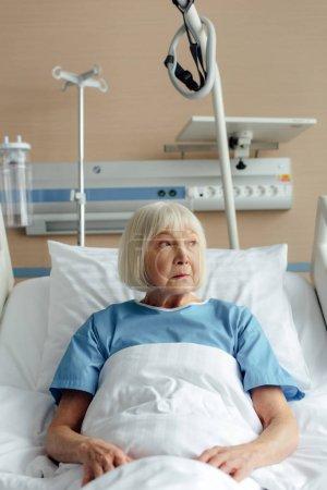 Photo pour Haute femme couché dans son lit à l'hôpital et de la recherche. - image libre de droit