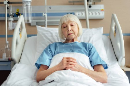 senior woman with folded hands lying in bed in hospital