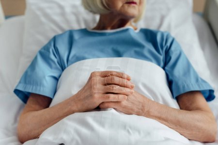 cropped view of senior woman with folded hands lying in bed in hospital