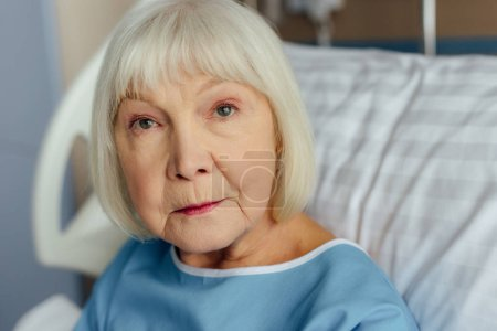 selective focus of sad senior woman with grey hair lying in bed in hospital