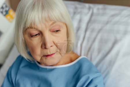 sad senior woman with grey hair lying in bed in hospital