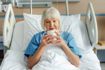 Photo pour Femme âgée couchée au lit et buvant du thé à l'hôpital - image libre de droit
