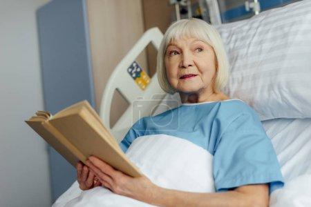 Foto de Mujer Senior con el pelo gris acostado en la cama y lectura en el hospital - Imagen libre de derechos