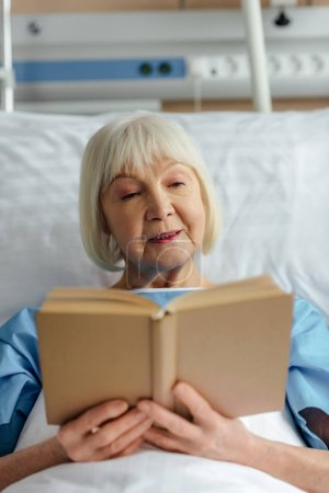 Photo pour Foyer sélectif de la femme âgée avec les cheveux gris couché dans le lit et le livre de lecture à l'hôpital - image libre de droit