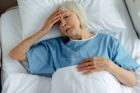 upset senior woman lying in hospital bed, touching forehead and having headache