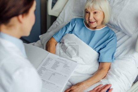 doctor holding diagnosis and consulting smiling senior woman lying in hospital bed