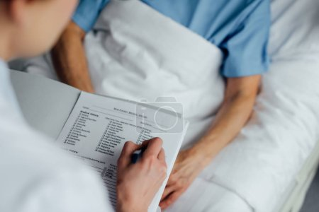 Photo for Cropped view of doctor holding diagnosis and consulting woman lying in hospital bed - Royalty Free Image