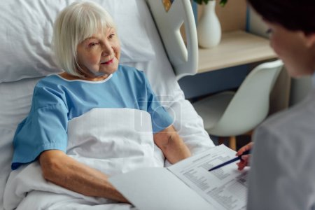 doctor holding diagnosis and consulting senior woman with grey hair lying in hospital bed