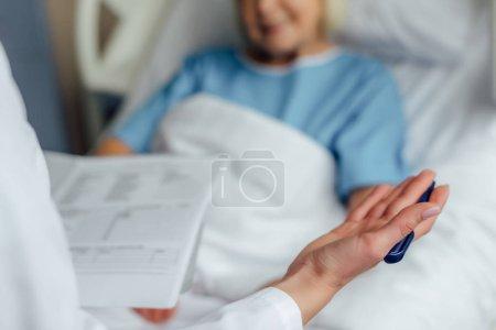 Photo pour Vue recadrée du médecin tenant le diagnostic et consultant le patient couché dans le lit d'hôpital - image libre de droit