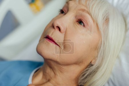 close up of upset senior woman with grey hair lying in bed and crying in hospital
