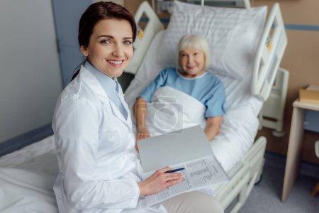 Photo pour Sourire de femme médecin assis sur le lit avec diagnostic et regardant la caméra tout en senior femme couché dans son lit à l'hôpital - image libre de droit