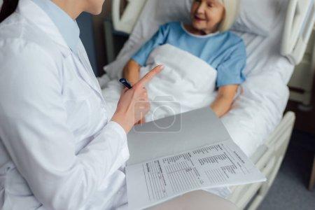 Photo pour Vue recadrée de femme médecin assis sur le lit, tenant diagnostic et pointer avec le doigt tout en senior femme couché dans son lit à l'hôpital - image libre de droit